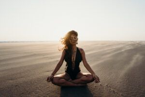 woman sitting on the beach, meditating