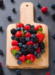different berries on a wooden plank