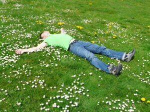 a man lying in a field with daisies on grass