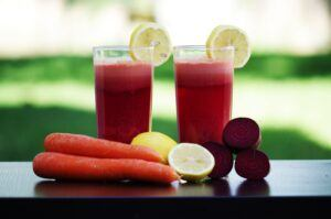 two glasses of juice, two carrots, lemons and beet root beside the glasses