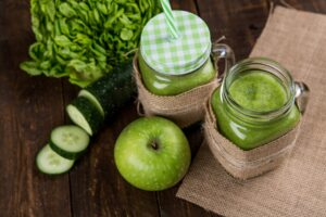 The health benefits of Juicing-Delicious  Juice, jars with green juice, apple and cucumber, lettuce beside the jars