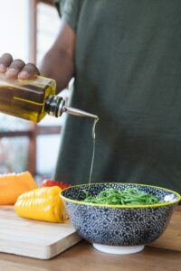 man putting oil in a salade
