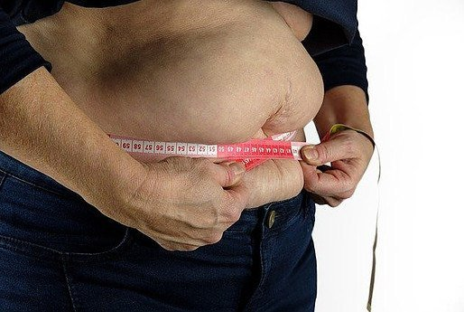 a man with a big belly, measuring the extent